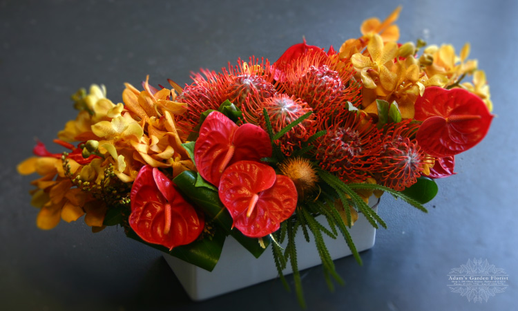 orange-red-and-yellow floral arrangement delivered gold coast
