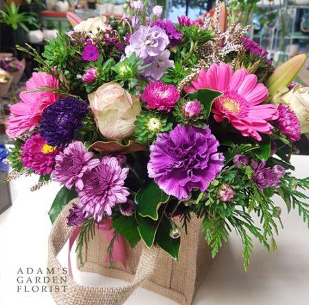 Floral arrangement in hessian bag. Medium, pink+purple. Gold Coast delivery.